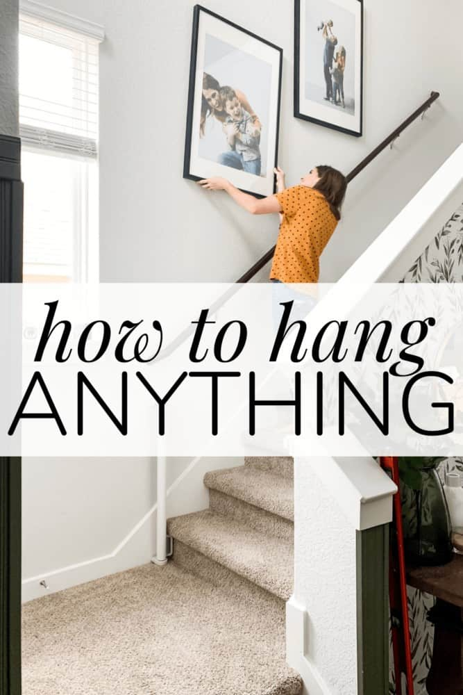 a woman hanging a piece of art on a staircase wall with a text overlay - how to hang anything