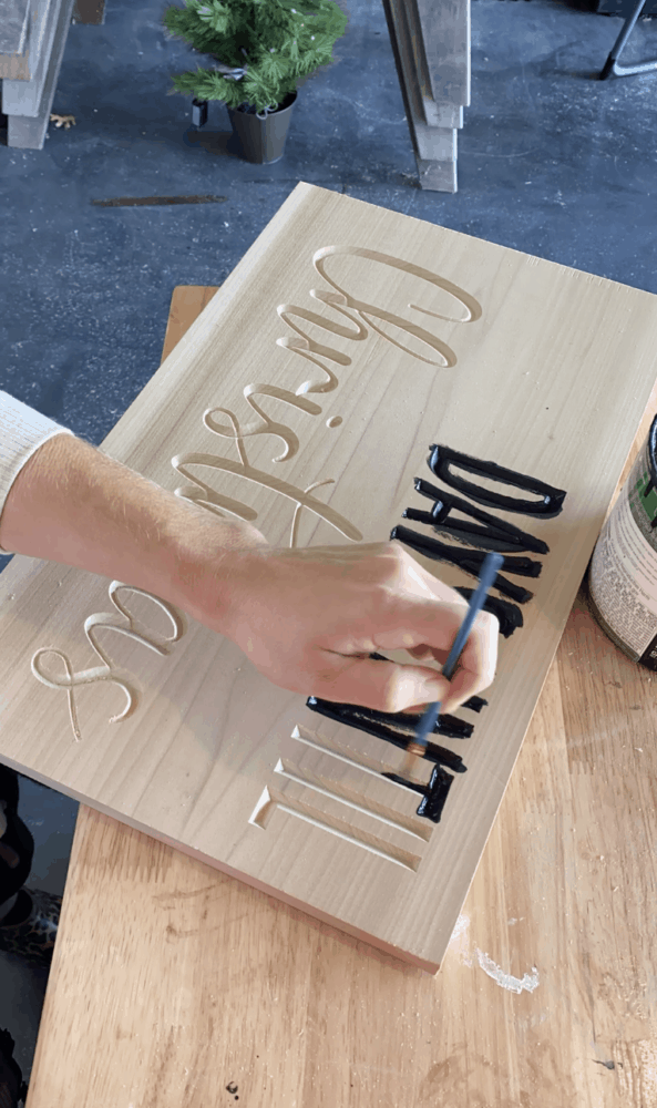 woman's hand painting a DIY carved wood Christmas countdown