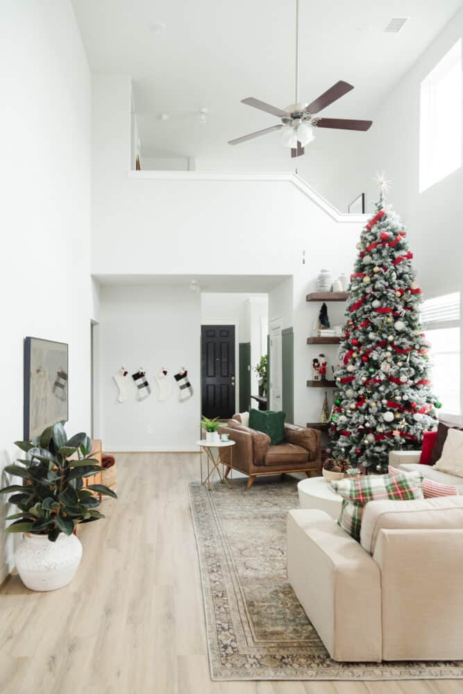 full view of cozy, neutral living room with a large Christmas tree