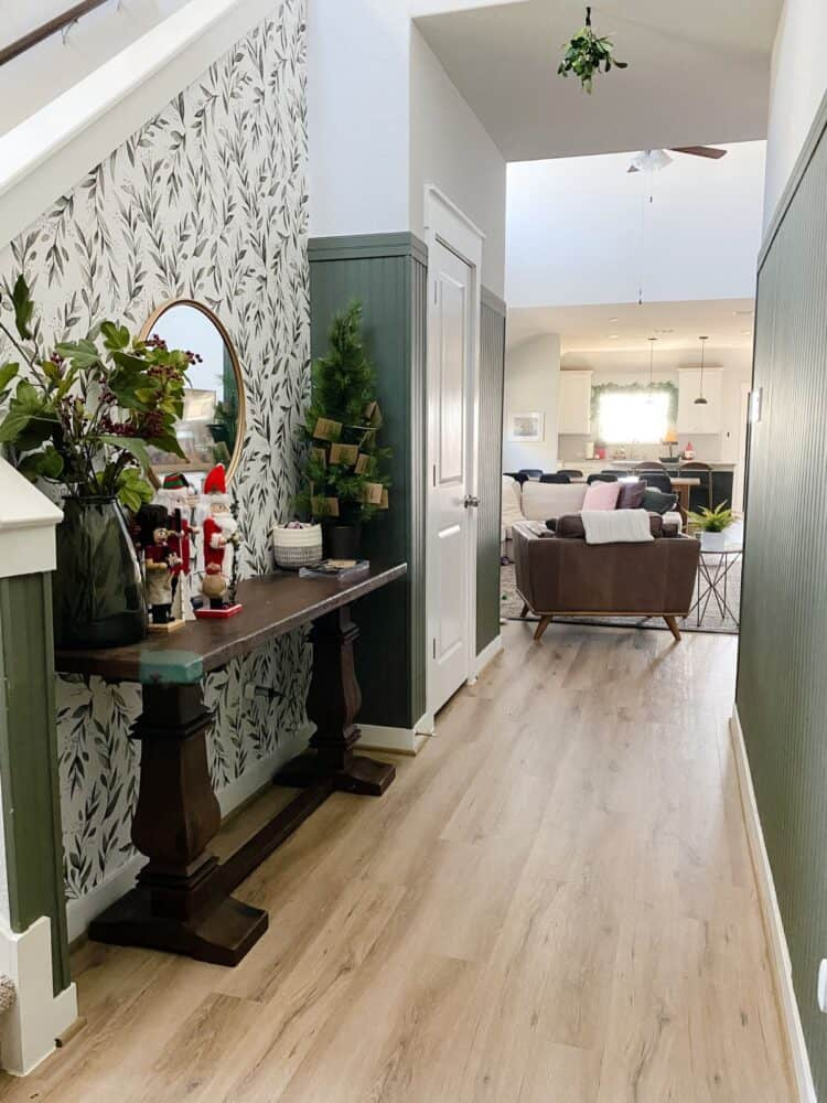 entry with green paneling and floral wallpaper, decorated for Christmas
