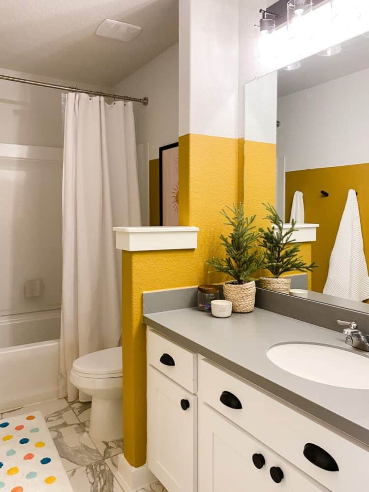 a small bathroom with yellow and white walls