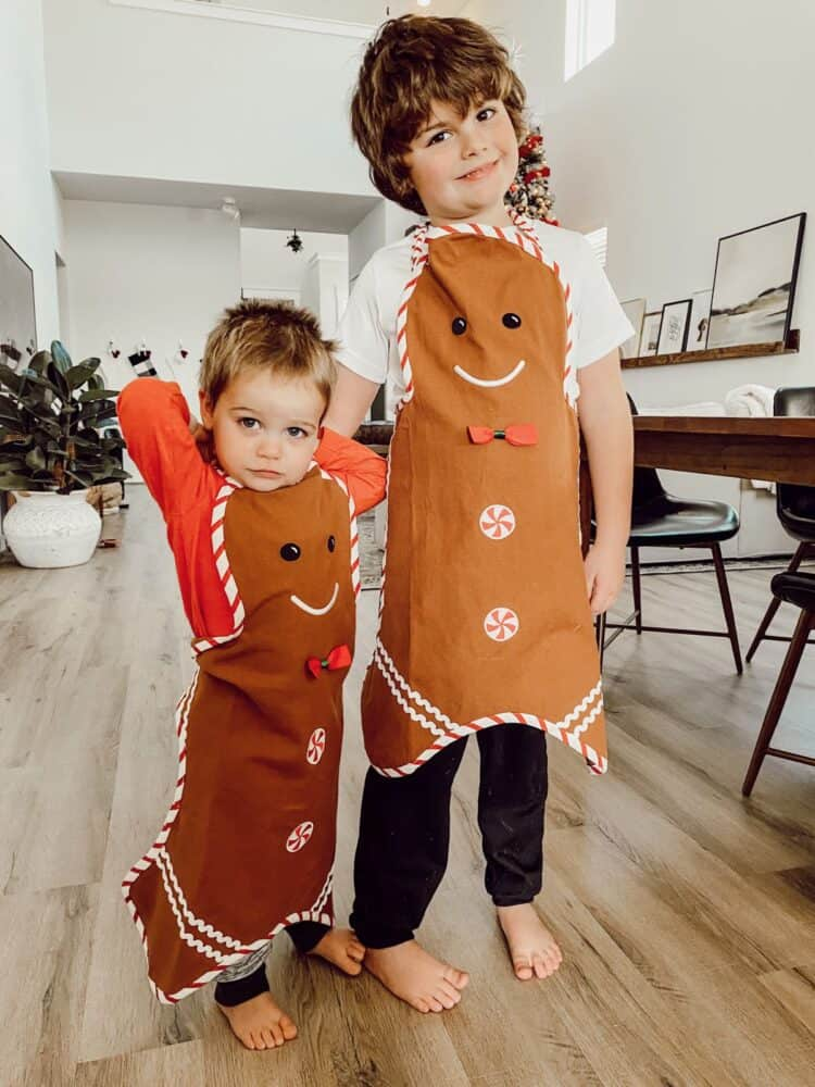 two young boys with gingerbread man aprons