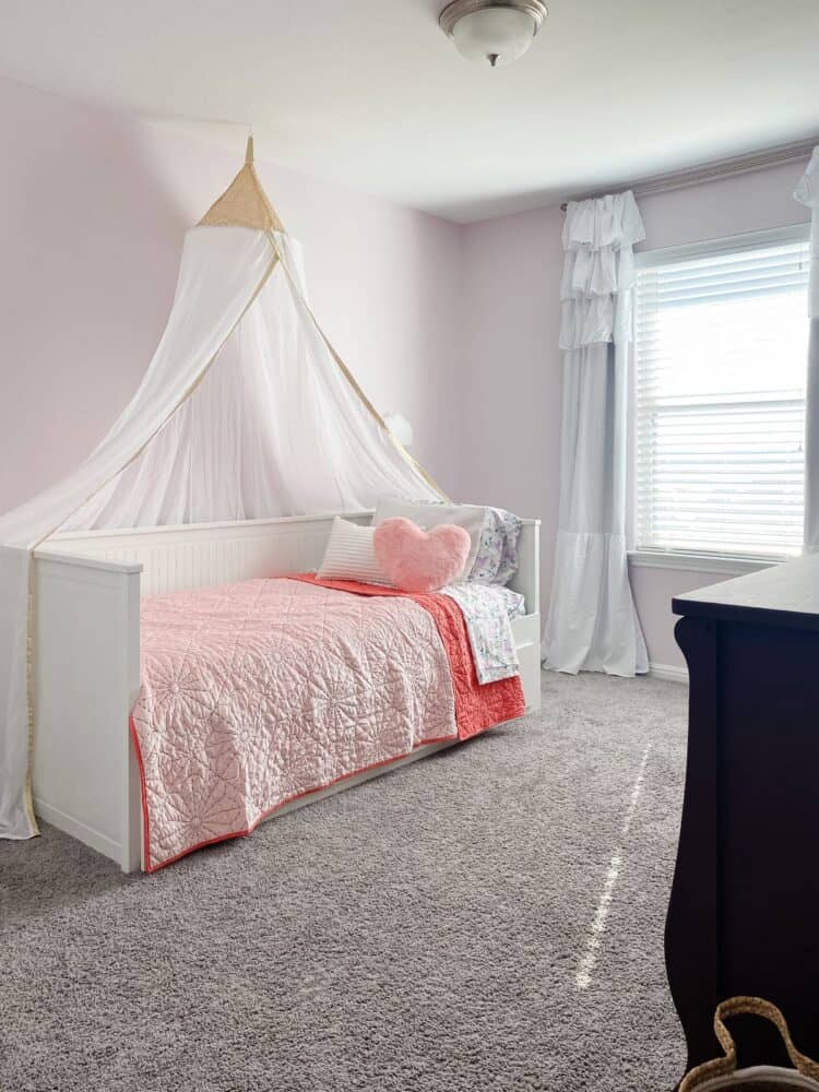 little girl's bedroom with princess canopy and rainbow mural