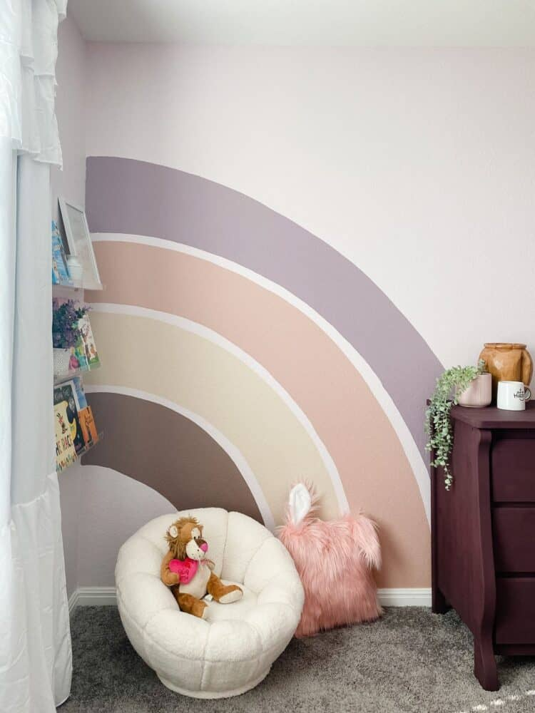 corner of princess themed bedroom with a rainbow mural and reading corner