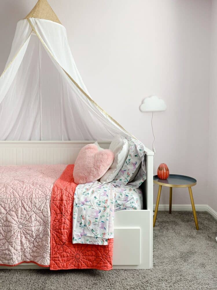 corner of girl's bedroom with pink bedding and princess canopy
