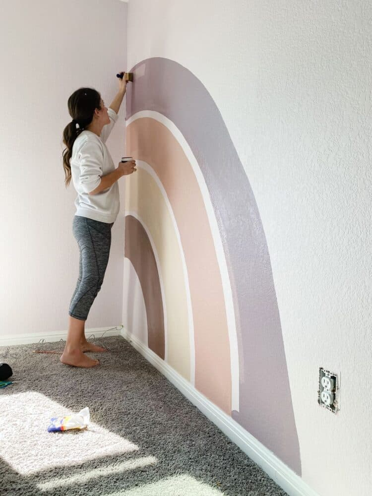 woman painting a rainbow mural