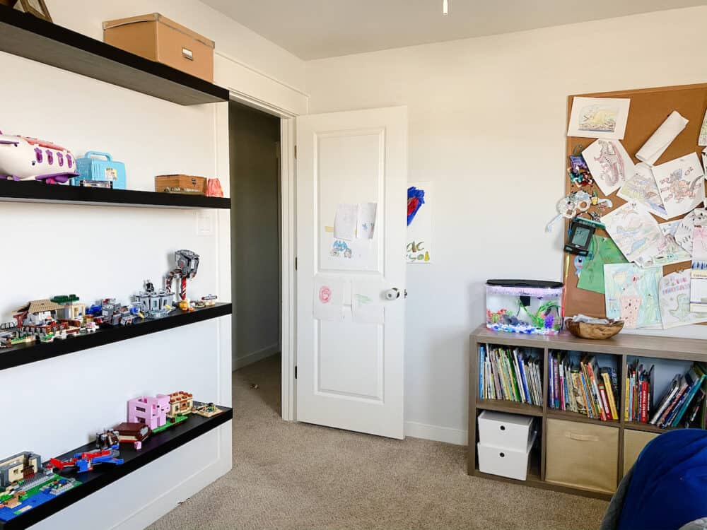 A kid bedroom with shelves on the wall