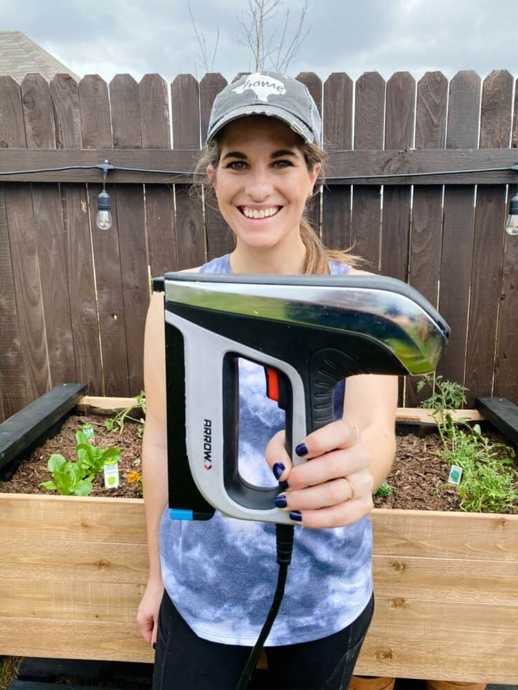 Woman holding an Arrow Fastener staple gun in front of a raised garden bed
