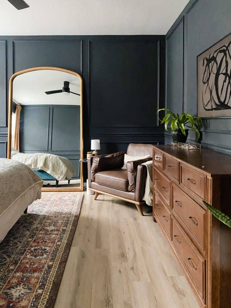Master bedroom with dark walls and trim, a huge gold mirror, and a cozy leather chair