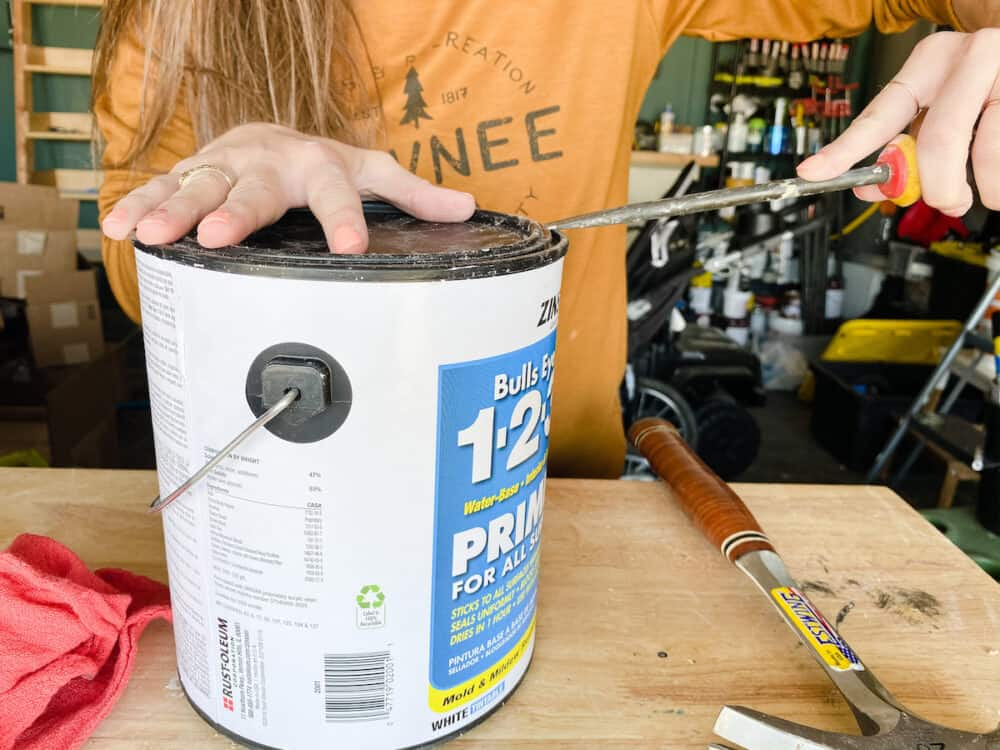 Close up of a paint can with a woman using a screwdriver to open it