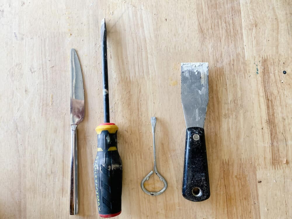 collection of tools that can be used to open a paint can