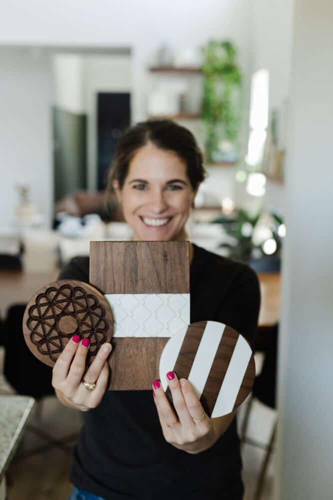 woman holding three wood and corian hot plates