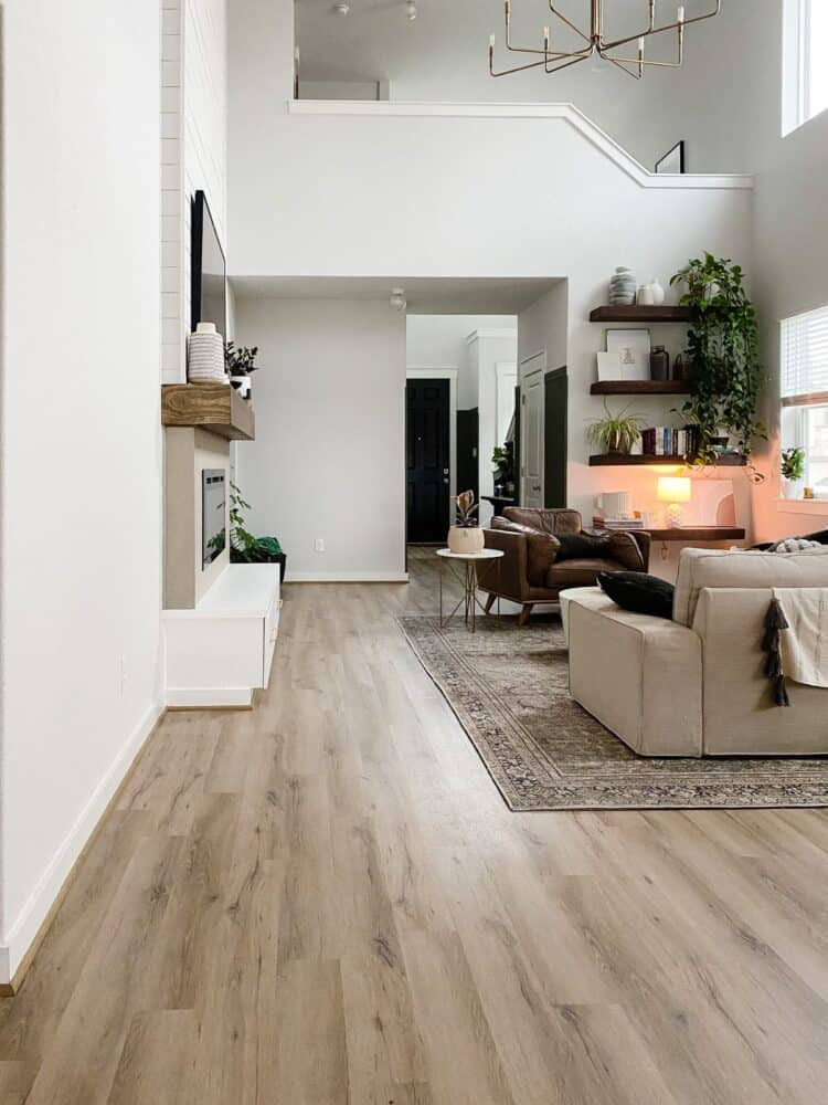 a neutral living room with tall ceilings and a shiplap fireplace