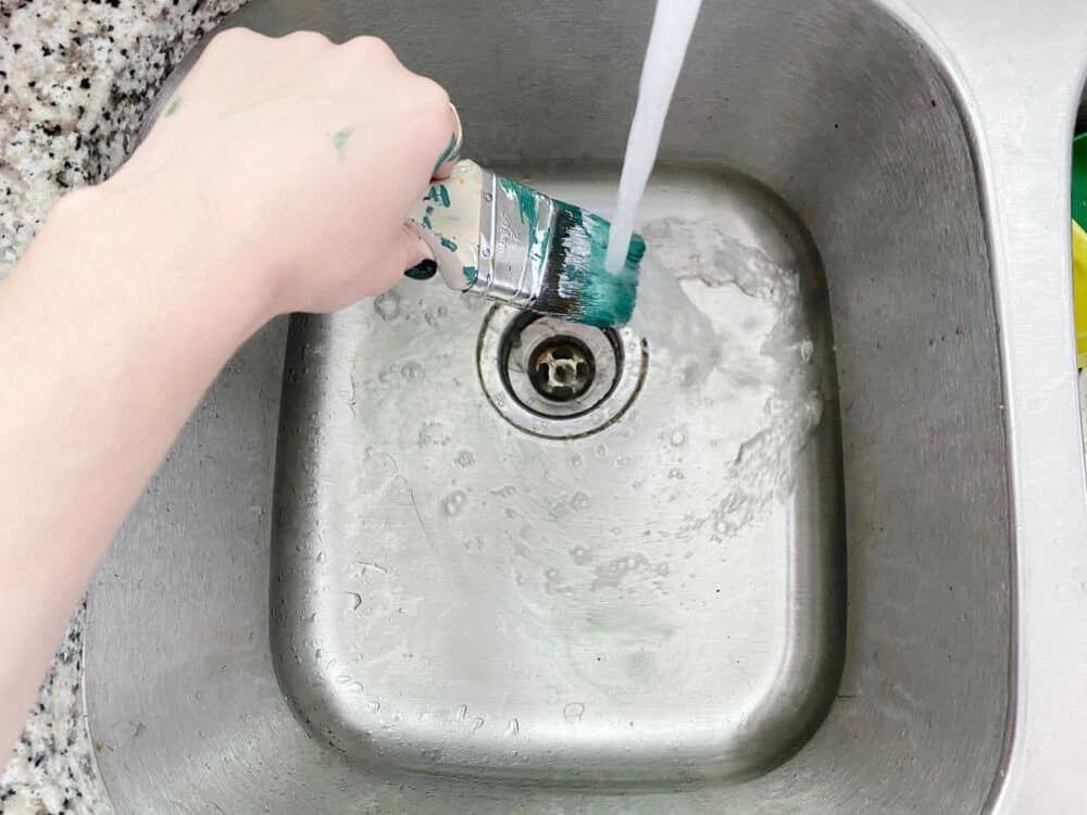 woman's hand rinsing a paintbrush