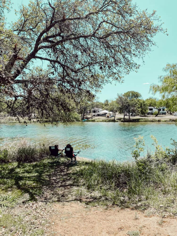 two boys sitting in camping chairs in front of a lake