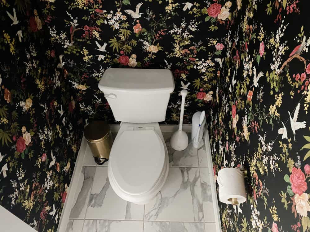 water closet with black floral wallpaper