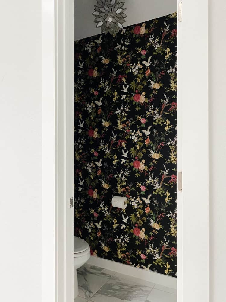 small water closet with black floral wallpaper