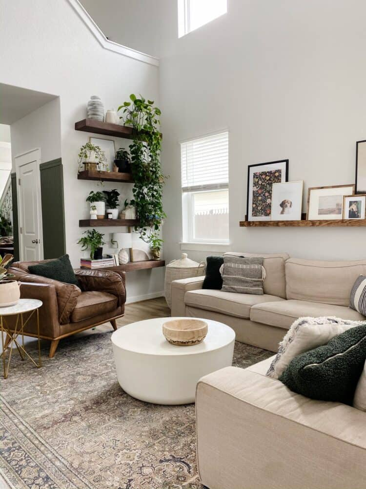 living room with a neutral color palette, floating shelves with lots of plants, and a large basket for throw blankets