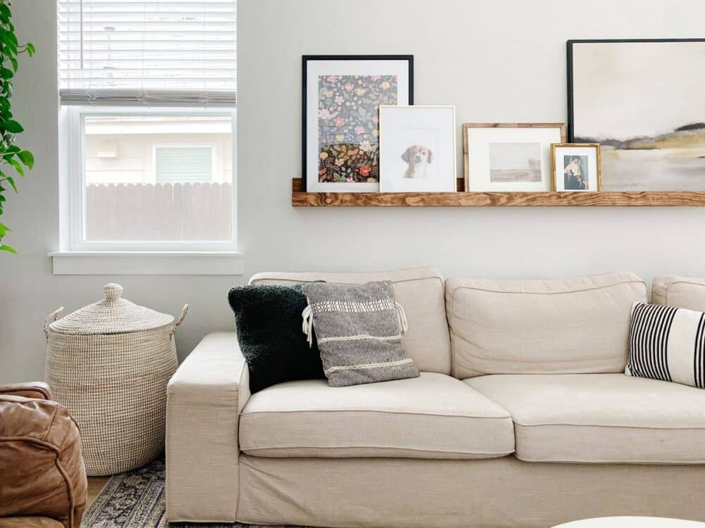 living room with a white sofa and a large basket for blankets