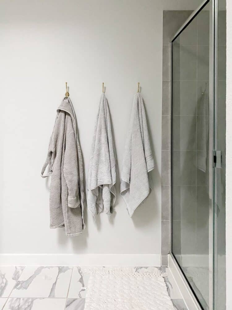 a white and gray bathroom with gold towel hooks hanging on the wall