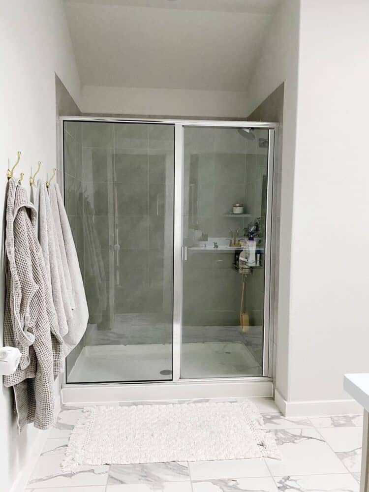 gray shower in a neutral bathroom with three gold towel hooks hanging on the wall
