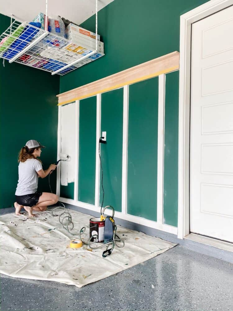 woman using a Wagner SMART Sidekick paint roller to paint a board and batten accent wall