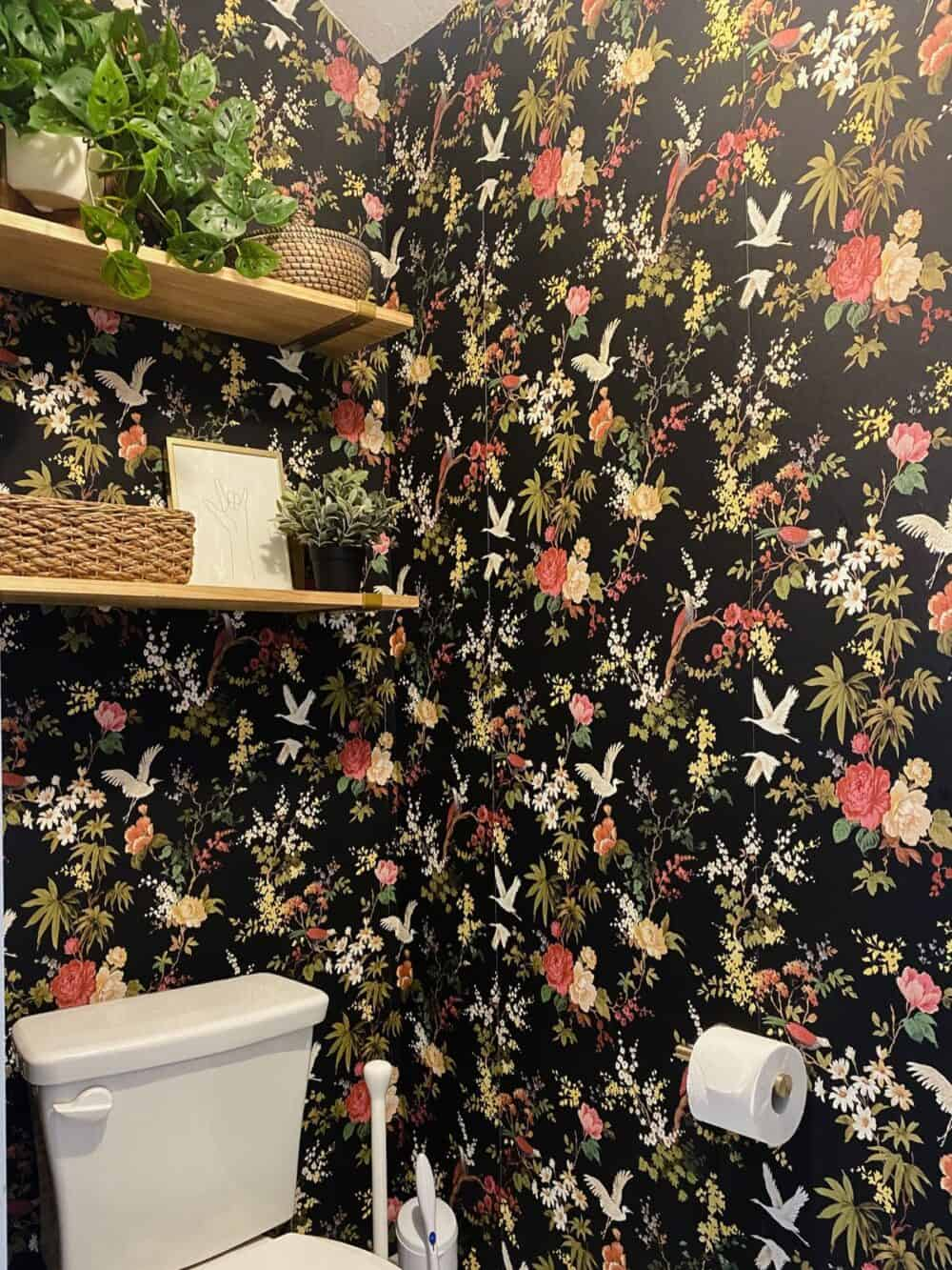 a small water closet with black floral wallpaper