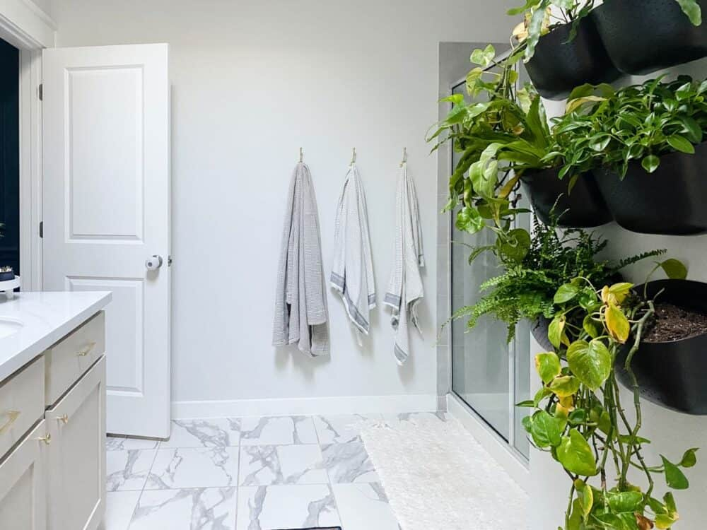 bathroom with plant wall and white faux marble tile