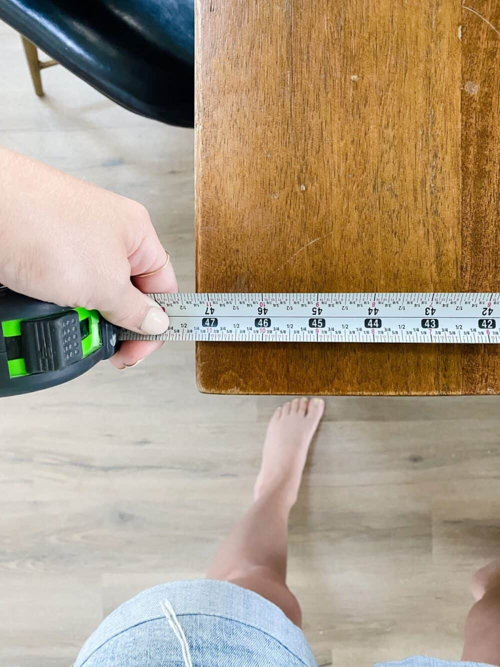 hang using a tape measure to measure a table