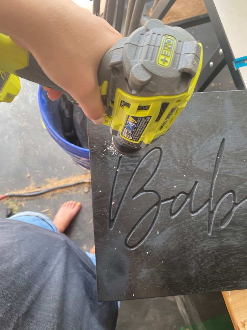 hand holding a Ryobi drill preparing to drill a hole in a DIY neon sign