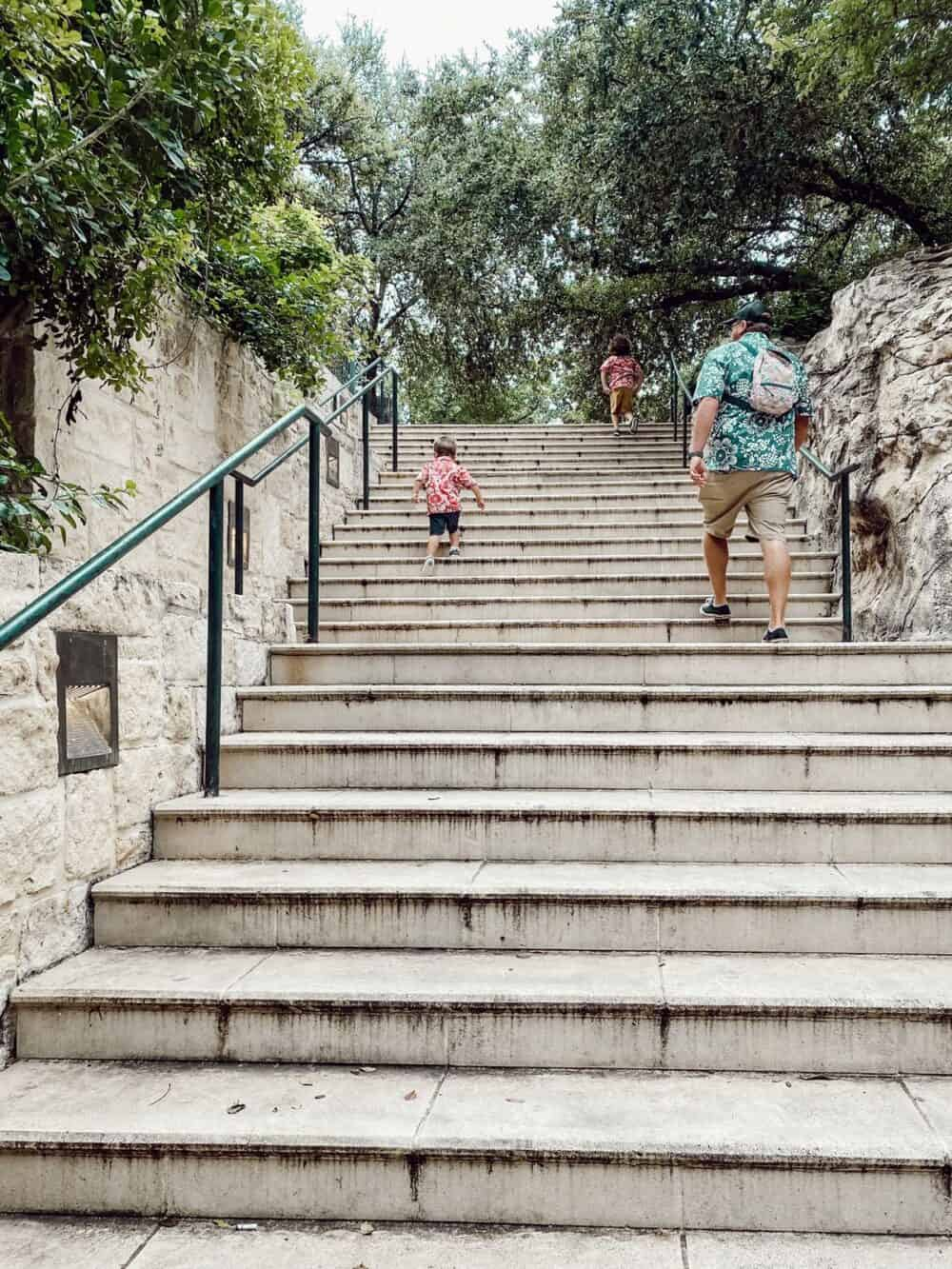 father and two young boys walking up a staircase at the SAn ANtonio riverwalk