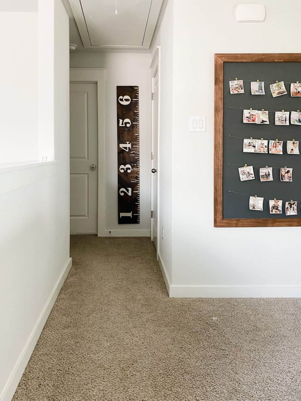 A small hallway with a wooden growth chart ruler hanging on the wall.