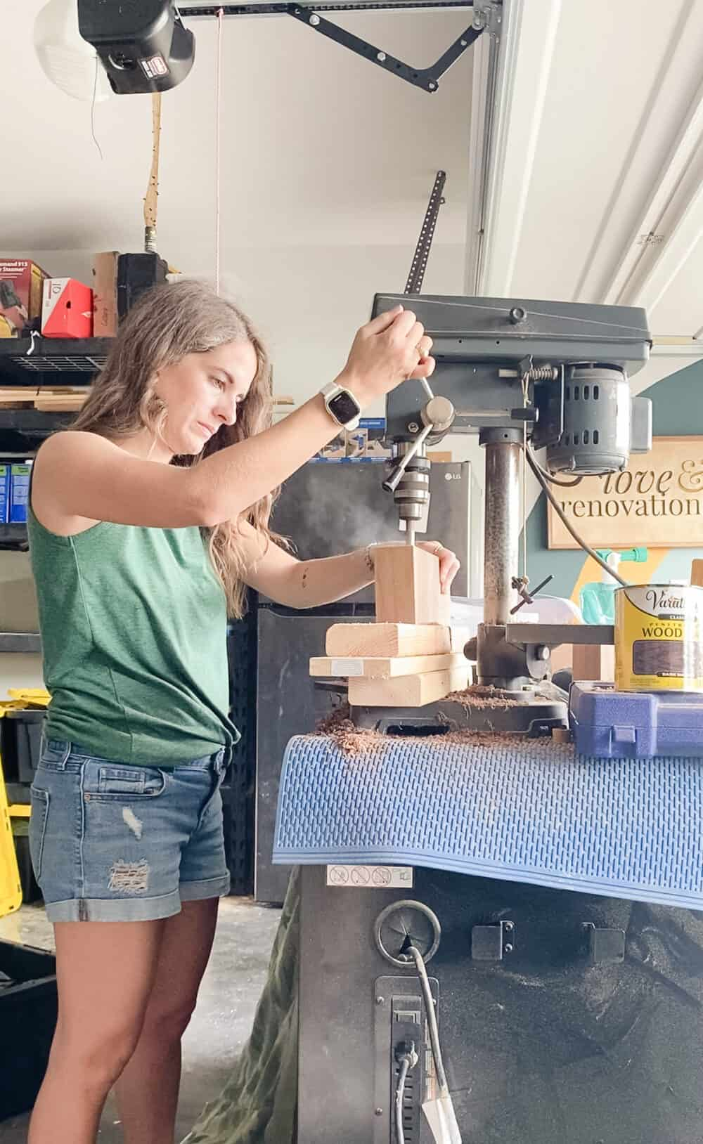 woman using a drill press to drill holes in a piece of walnut