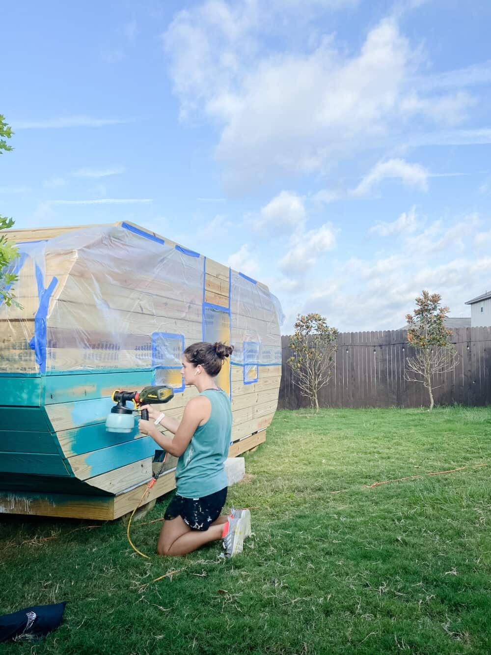 Woman painting a playhouse with a Wagner paint sprayer