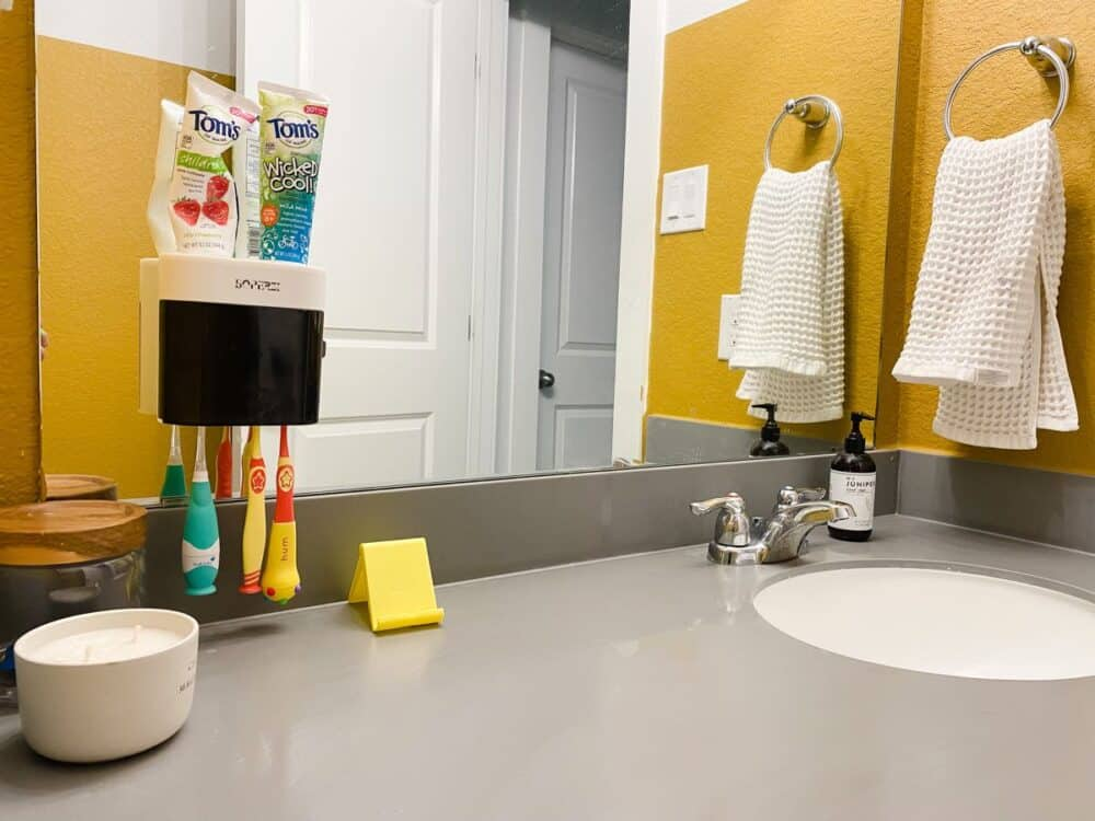 Bathroom with toothbrush holder on mirror