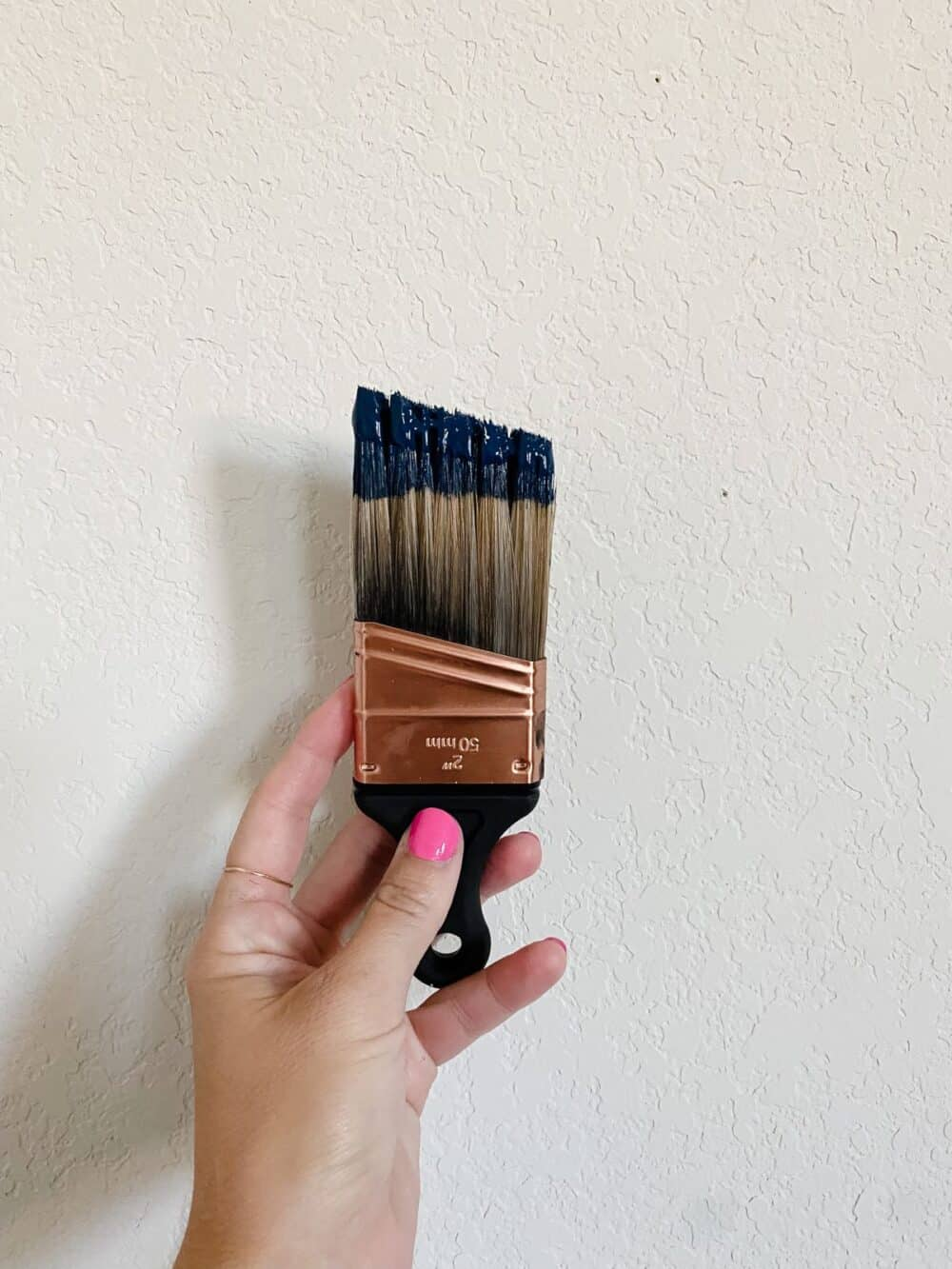 Woman's hand holding a paint brush with navy blue paint on it