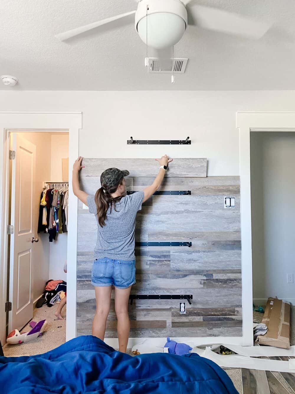 Woman installing vinyl planks on accent wall