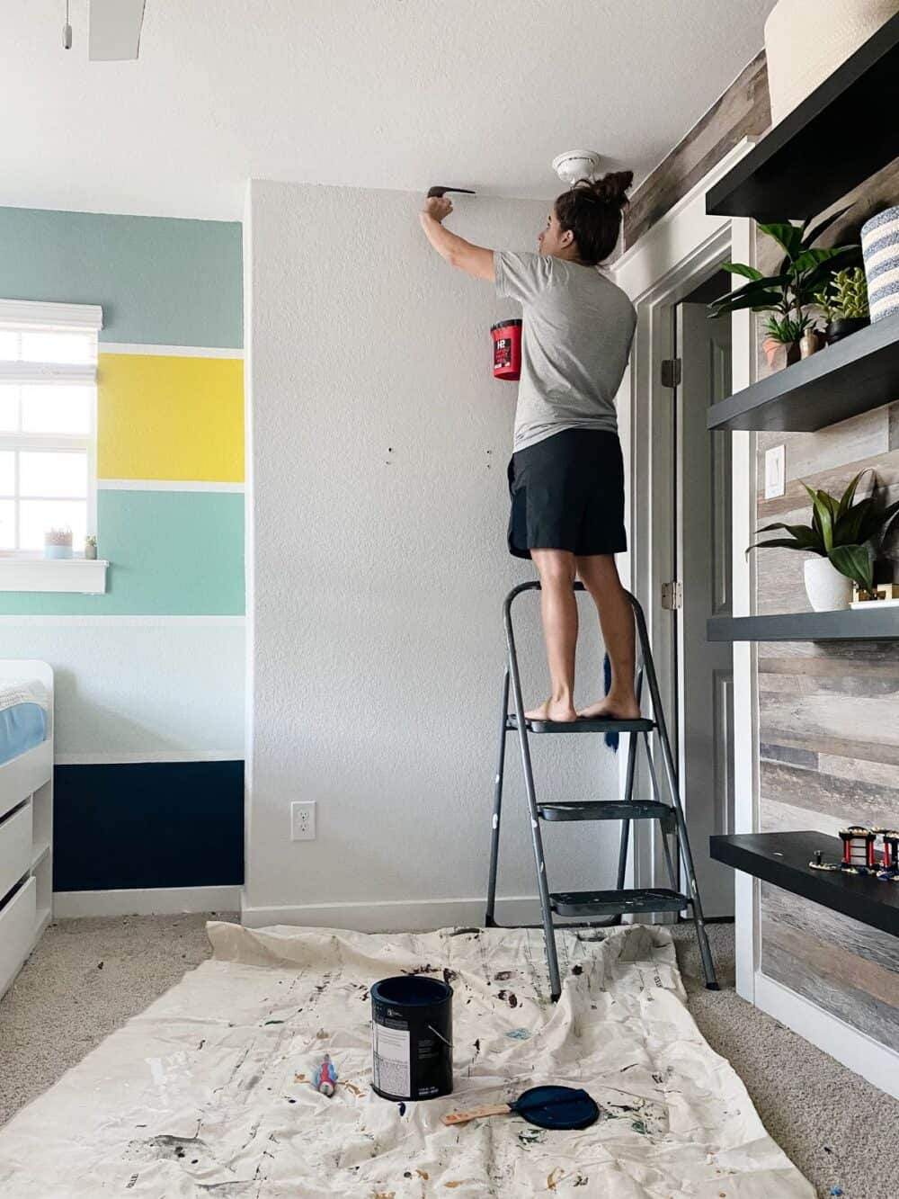 Woman cutting in edges around ceiling to paint ceiling