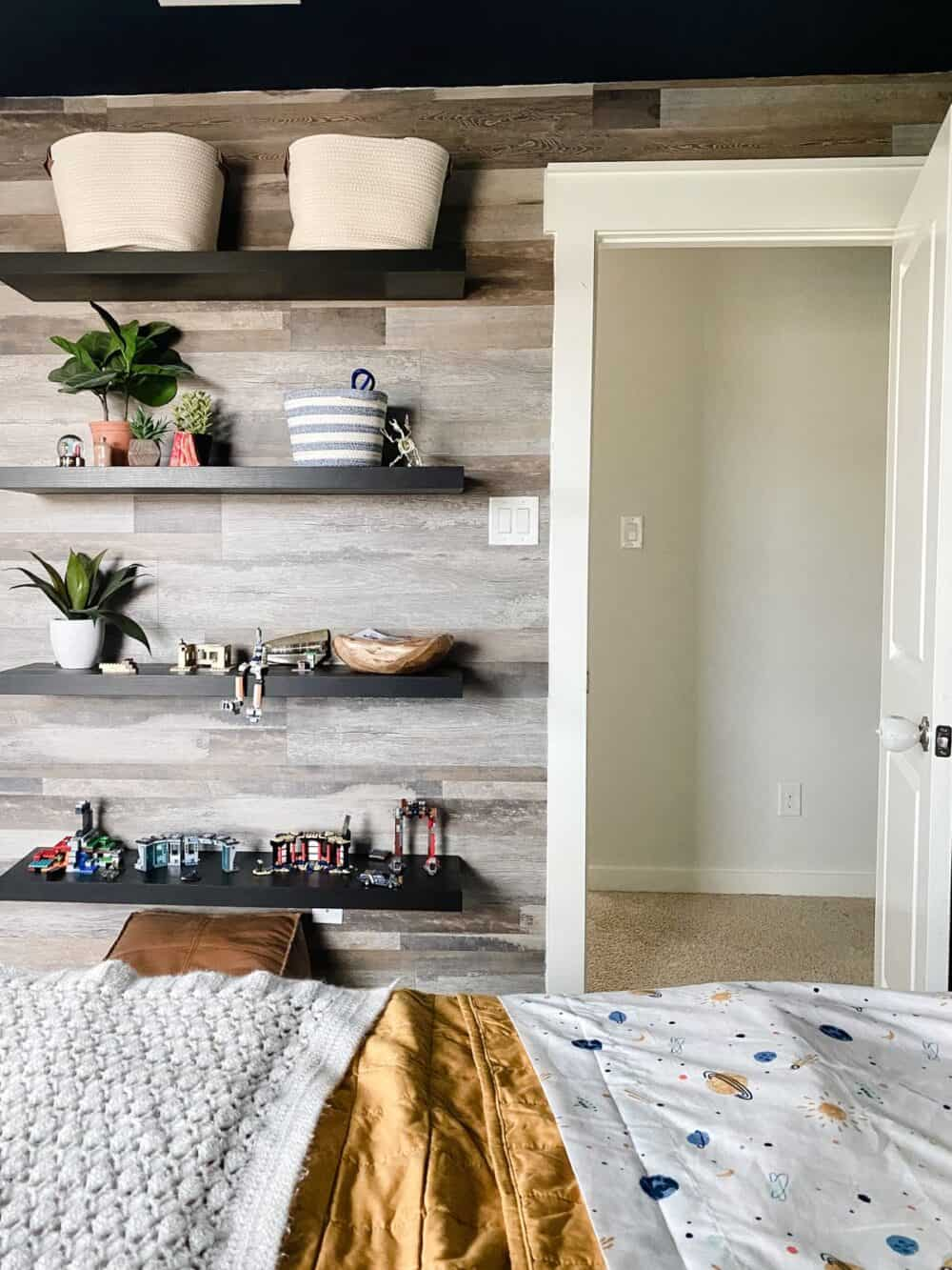 A boys' bedroom with a faux wood vinyl plank accent wall