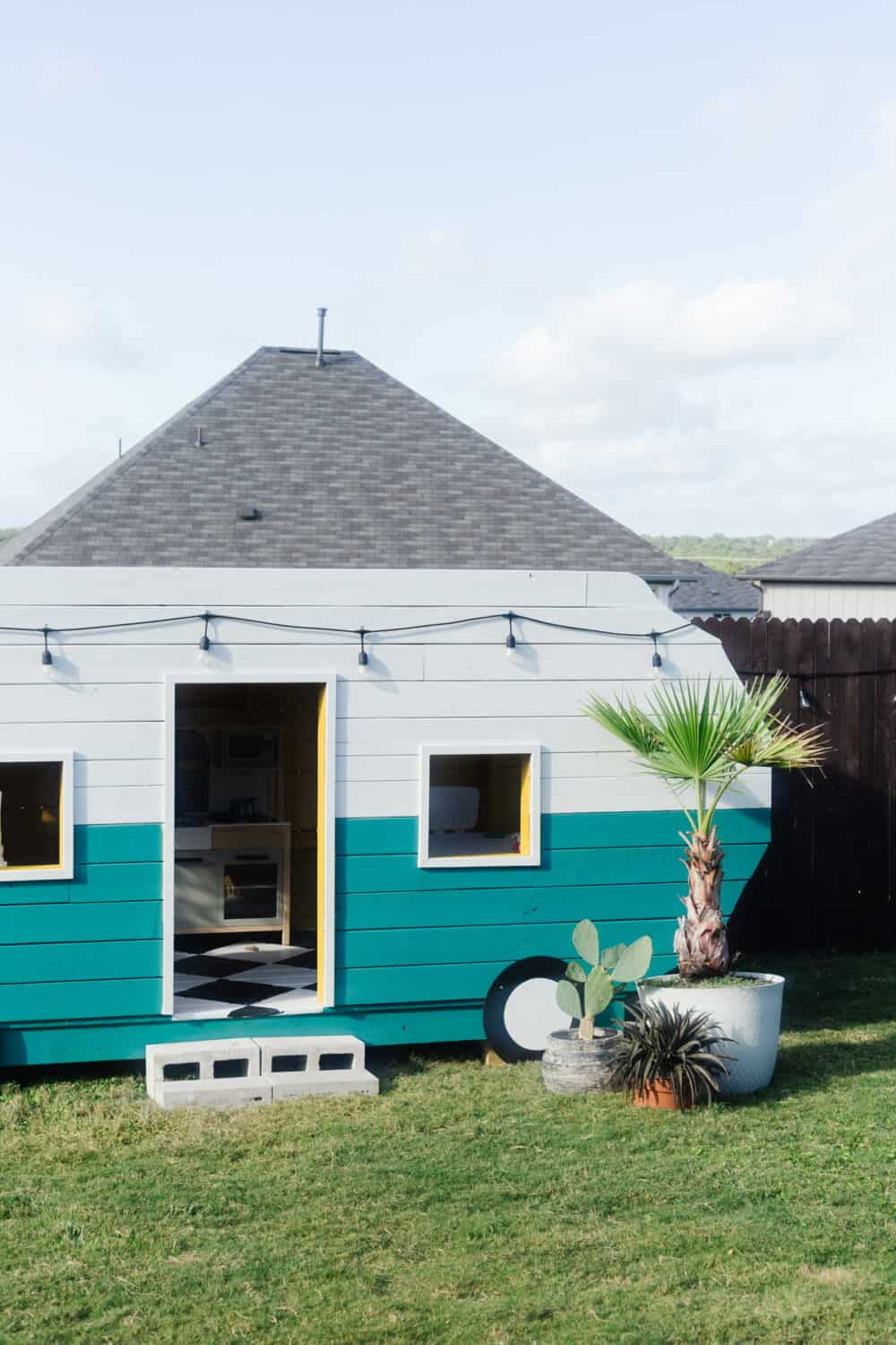 A playhouse shaped and styled like a vintage camper