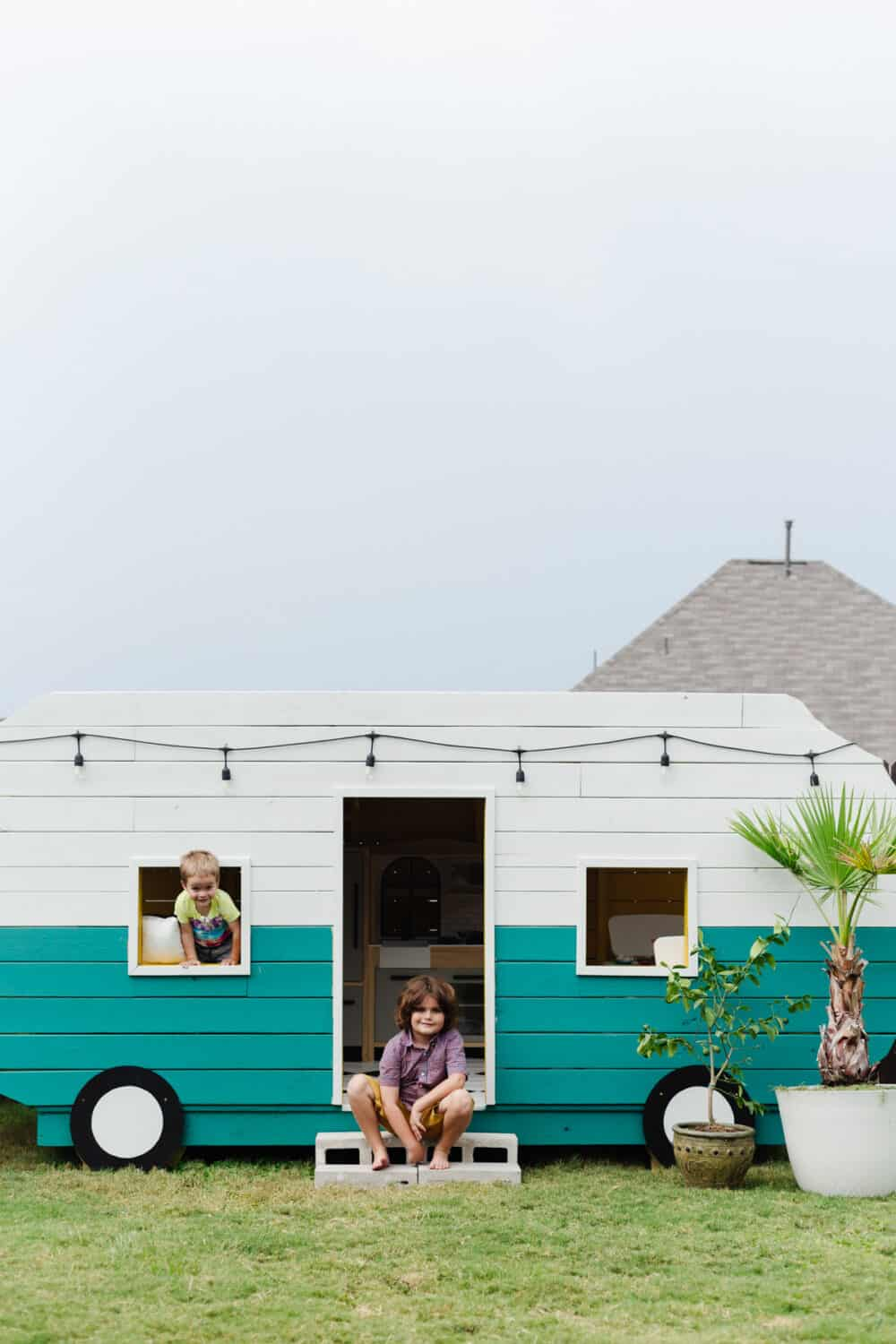 Two young boys posing with a playhouse camper