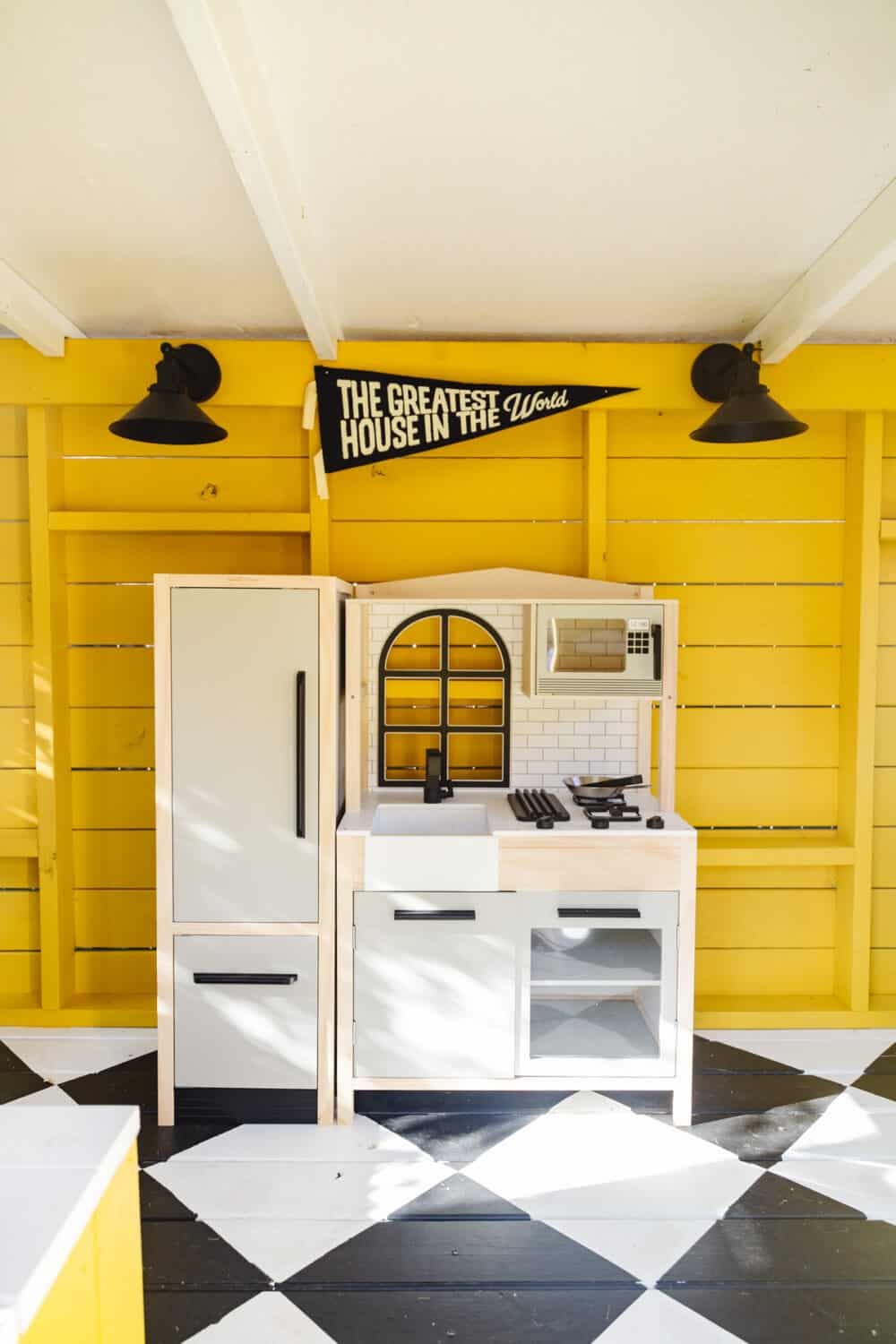 Small play kitchen inside an exterior playhouse