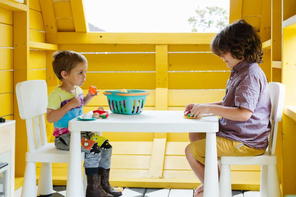two young boys playing in a seating area of a camper playhouse