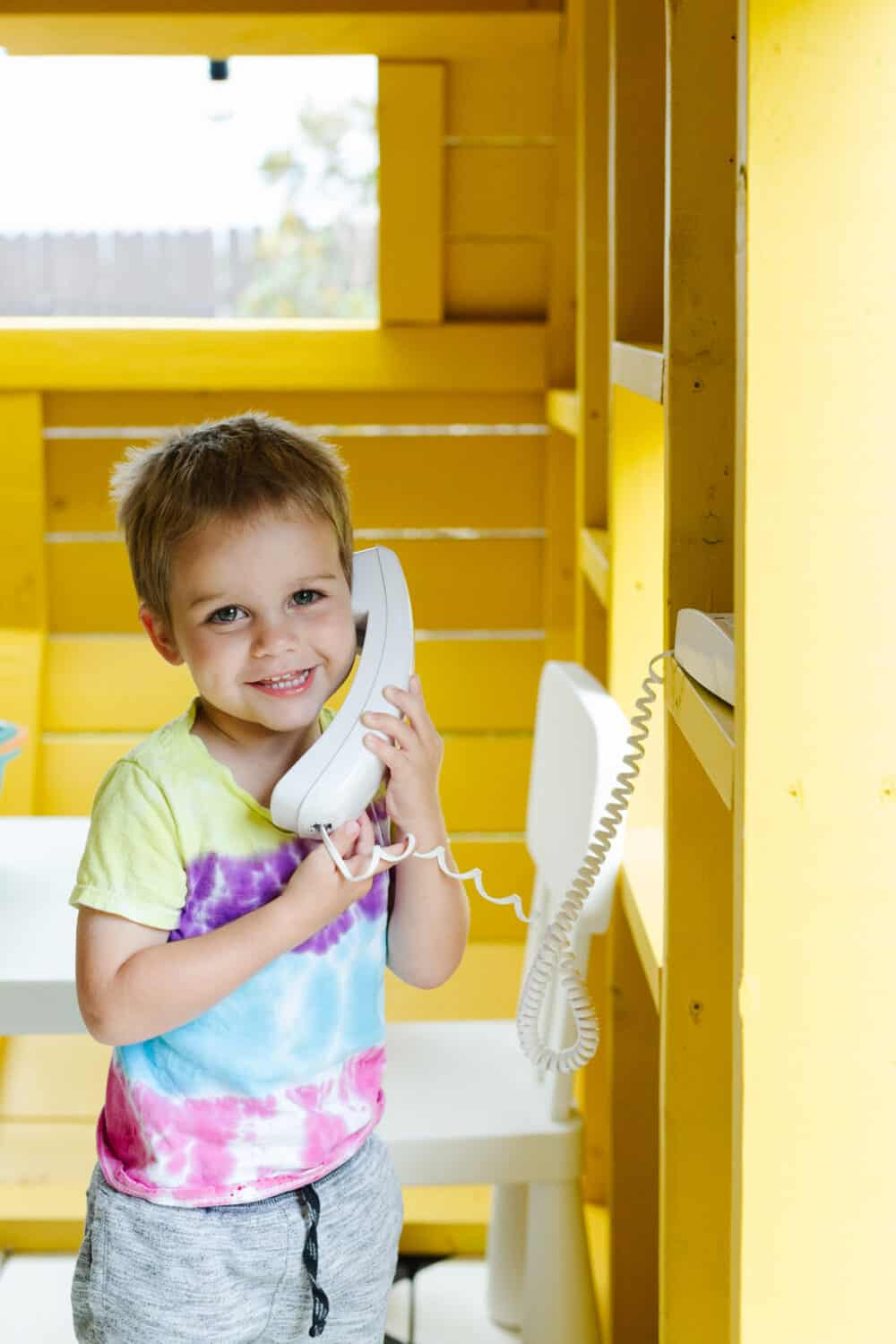 toddler on a play telephone