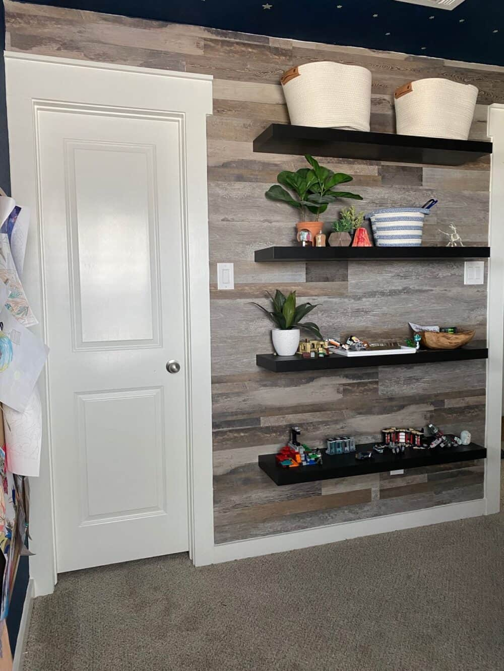 A child's bedroom with a faux wood accent wall