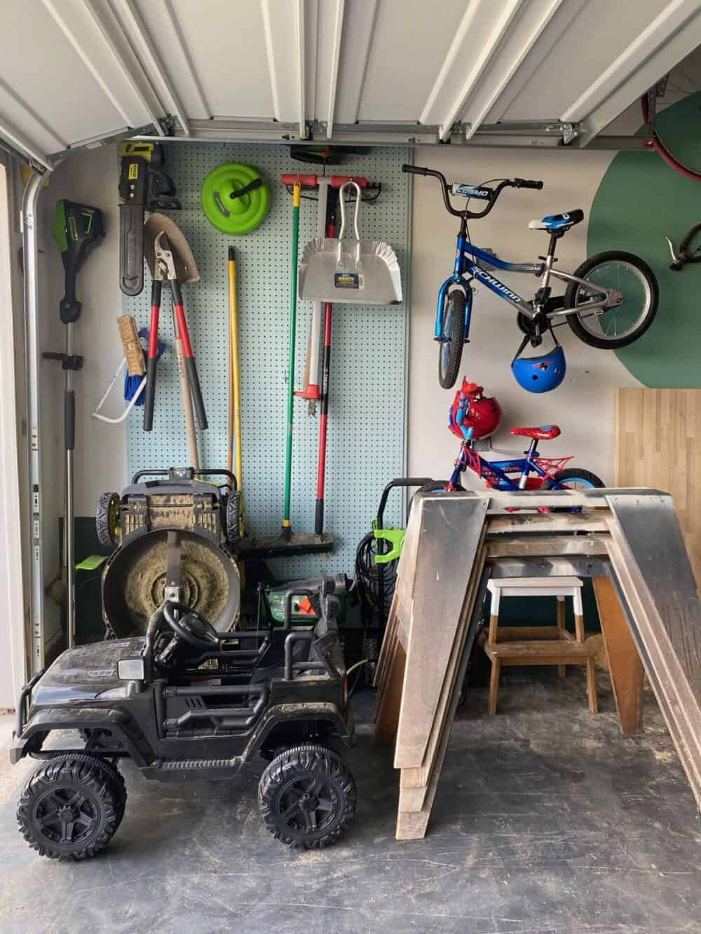 Large pegboard with lawn equipment hung on it