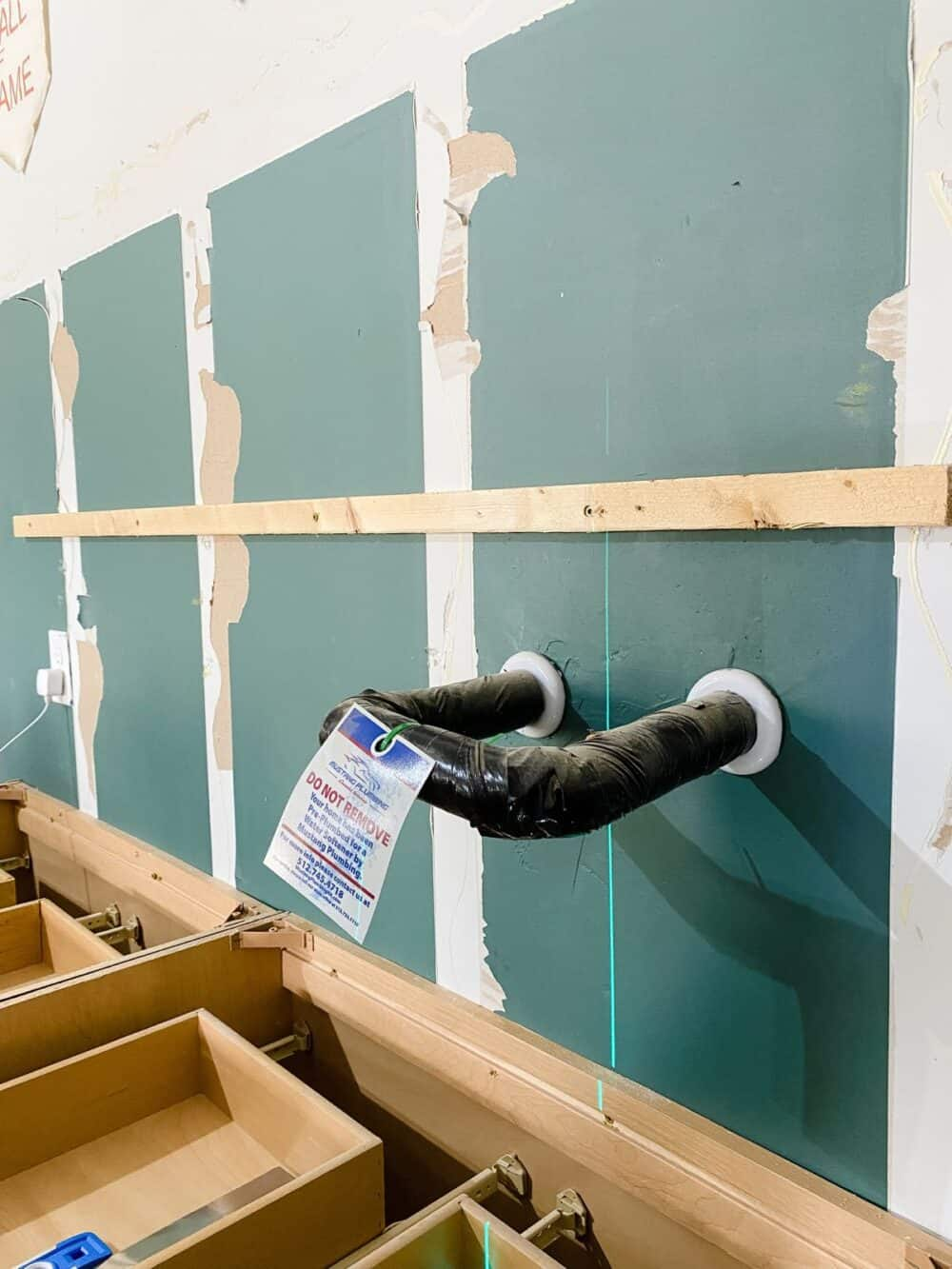 Ledger board installed on a wall for garage cabinets
