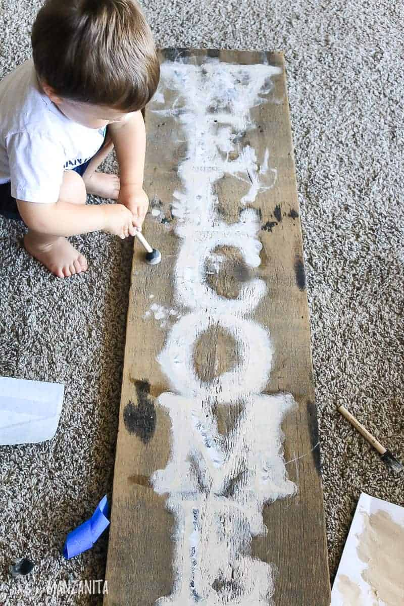 Toddler helping paint welcome sign for front porch