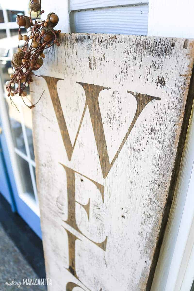 Close up of stenciled letters on rustic wooden sign that says welcome
