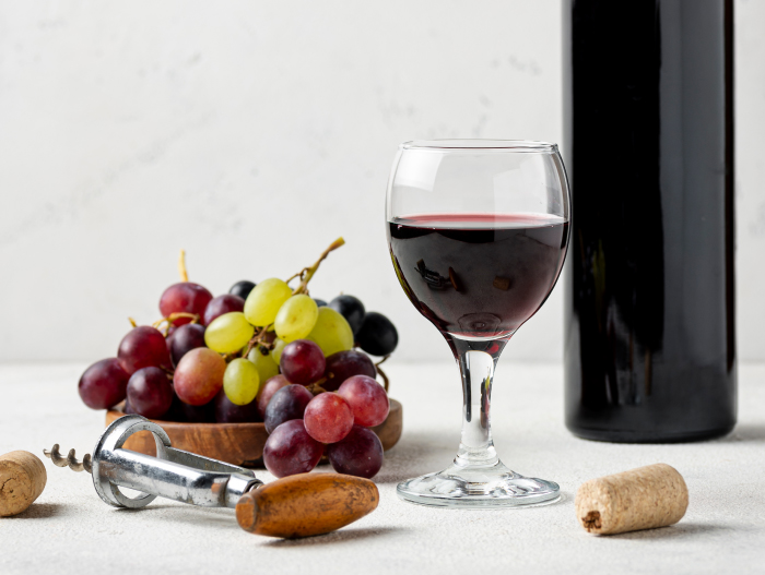 Grapes and red wine with a wine bottle on a white table